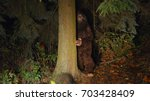 Stock photo sasquatch looks out from behind a tree in the forest 703428409