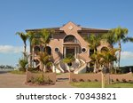 Huge, three story, mediterranean waterfront mansion. Dual stairs leads to the double columned entryway. Palm trees frame the house. The cobblestone driveway creates a welcome mat for its visitors. - stock photo