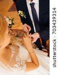 groom puts wedding ring on... | Shutterstock . vector #703439314