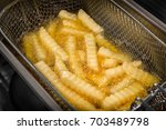 deep frying french fries in the ... | Shutterstock . vector #703489798