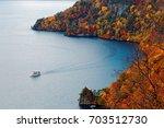 Stock photo aerial view of a sightseeing boat cruising on lake towada in beautiful autumn season in towada 703512730