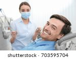 handsome man at dentist's office | Shutterstock . vector #703595704