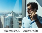 young businessman speaking on... | Shutterstock . vector #703597588