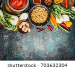 Small photo of Vegetarian cooking ingredients with chick peas dish, spicy indian curry paste , greens, ginger and vegetables on rustic background, top view, border. Healthy food and eating or Indian cuisine concept