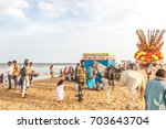 Small photo of Group of people gathered at Marina beach, having fun in the ocean waves with beautiful clouds in sky,sellers seen selling eatables by seashore, and horse ride for kids,Chennai,India 19 aug 2017