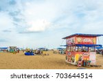 Small photo of Group of people gathered at Marina beach with beautiful clouds in sky,sellers seen selling eatables by seashore,Chennai,India 19 aug 2017