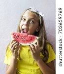 a cute girl holding a ripe... | Shutterstock . vector #703659769