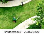 man worker cutting  grass with...   Shutterstock . vector #703698229