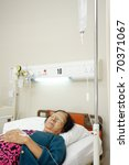 asian ethnic old patient woman bed rest in hospital ward - stock photo