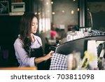 asian women barista smiling and ... | Shutterstock . vector #703811098