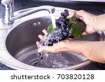 man's hands washing a fresh...   Shutterstock . vector #703820128