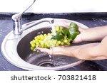 man's hands washing a fresh...   Shutterstock . vector #703821418