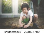 cute asian child planting young ... | Shutterstock . vector #703837780