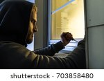 male young robber in hood using ... | Shutterstock . vector #703858480