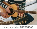 learning to play the guitar.... | Shutterstock . vector #703900060