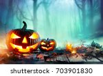 Stock photo pumpkins burning in forest at night halloween background 703901830