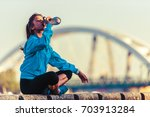 young woman jogger resting...   Shutterstock . vector #703913284