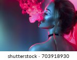 Stock photo fashion art portrait of beauty model woman in bright lights with colorful smoke smoking girl 703918930