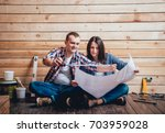 happy couple making repairs to... | Shutterstock . vector #703959028