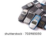 old and obsolete cellphone on a ... | Shutterstock . vector #703985050