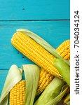 ripe yellow sweet corn cob on a ... | Shutterstock . vector #704034124