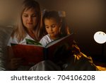 mother and child girl reading a ... | Shutterstock . vector #704106208