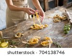 raw homemade pasta and hands... | Shutterstock . vector #704138746