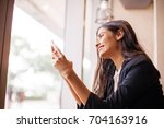 indian woman with mobile phone... | Shutterstock . vector #704163916