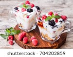 yogurt with muesli and berries... | Shutterstock . vector #704202859