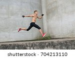 young man running on grey... | Shutterstock . vector #704213110
