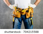 Small photo of unknown handyman with hands on waist and tool belt with construction tools against grey background. DIY tools and manual work concept