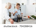 happy young woman cooking... | Shutterstock . vector #704288416