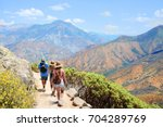 Family with backpacks on hiking trip , High mountains landscape with cloudy sky. Kings Canyon National Park, Fresno, California, USA - stock photo