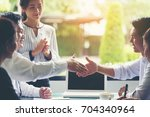 the business team is shaking... | Shutterstock . vector #704340964