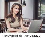 happy woman using laptop at... | Shutterstock . vector #704352280