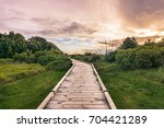 green meadow and the road... | Shutterstock . vector #704421289