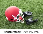 a red football helmet sits on a ... | Shutterstock . vector #704442496