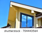 photo of part of a wooden house | Shutterstock . vector #704443564
