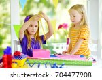 two cute sisters wrapping gifts ... | Shutterstock . vector #704477908