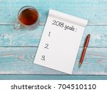 notebook with new years goals... | Shutterstock . vector #704510110