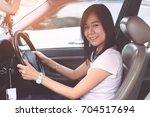 beautiful woman driving a car... | Shutterstock . vector #704517694