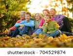big family sitting on ground  | Shutterstock . vector #704529874