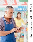 Small photo of Confident supermarket clerk working with a digital tablet, technology and work concept