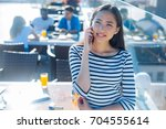 cheerful girl talking on phone... | Shutterstock . vector #704555614