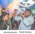 Stock photo young friends dancing at party in night club soft focus on black man 704574916