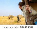 woman on safari game drive... | Shutterstock . vector #704595604
