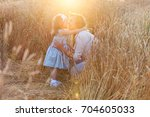 Small photo of Happy mother holding and hugging her little daughter smiling on a wheat field in sunlight and sunset outdoor on nature