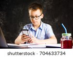 boy playing the phone while... | Shutterstock . vector #704633734