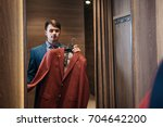 buyer tries  red color of the... | Shutterstock . vector #704642200