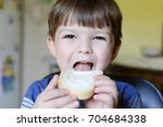 boy eating bread with cream... | Shutterstock . vector #704684338